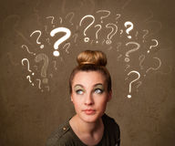 Girl with question mark symbols around her head Royalty Free Stock Photo