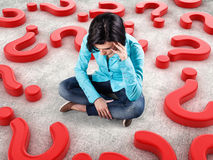 Girl among questions. Sad girl sits among many red questions Royalty Free Stock Photo