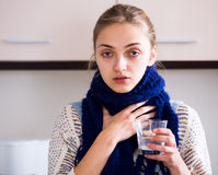 Girl with quinsy taking medicine Royalty Free Stock Photography
