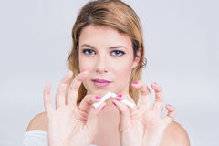 Girl quits smoking. Angry blonde woman breaking a cigarette Stock Image