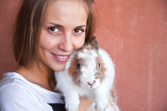 Girl with a rabbit. Cute smiling girl holding a little fluffy bunny Royalty Free Stock Photo