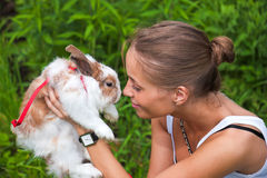 Girl with a rabbit. A girl plays with a rabbit on green grass Stock Photos