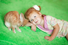 Girl with rabbit. Casual portrait of a little red-haired girl with a small rabbit Stock Photography