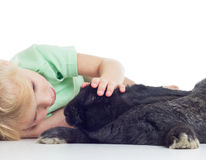 Girl with rabbit. Little blond girl petting a black rabbit on white background Stock Image