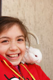 Girl and rabbit. Cute girl and white baby rabbit on her shoulder royalty free stock photo