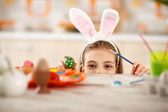 Girl with rabbit ears on head show colorful Easter egg. Girl with rabbit ears on head sticking under table and show colorful Easter egg Royalty Free Stock Images