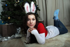 Girl with rabbit ears lies resting near a tree Stock Photo