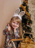 Girl with rabbit ears showing ok over Christmas tree Stock Photography