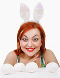 Girl with rabbit ears surprise. eyes increased for comic effect. Girl with rabbit ears stares at the eggs on the table.The girls eyes artificially are increased Royalty Free Stock Photography