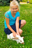 Girl with rabbit. Girl petting a bunny who is sitting in the grass royalty free stock images