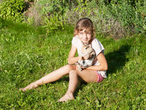 Girl with rabbit sitting on the meadow Stock Images