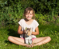 Girl with rabbit sitting on the meadow Royalty Free Stock Photos