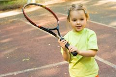Girl with racket. Nice girl with racket in hands playing game of tennis Royalty Free Stock Photo