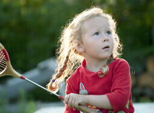 Girl with a racket. The little girl plays with a racket in badminton. Shallow DOF Stock Photo