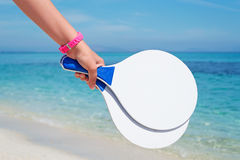 Girl with racket. Girl holding a white beach racket Stock Images
