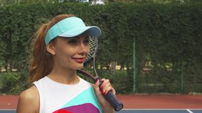 Girl with a racket smiling and looking at camera stock footage