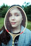The girl with the racket. Girl in a suit holding a racket. She`s a beautiful model stock photos