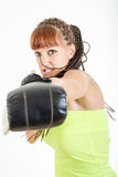 Girl in rage wearing boxing gloves ready to fight and punching o Royalty Free Stock Photo