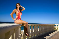 Girl on a rail near the ocean with blue sky Royalty Free Stock Photography
