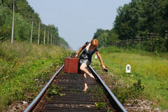 Girl on the railroad track with suitcase Stock Image