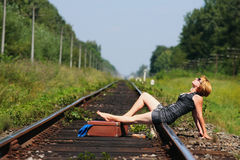 Girl on the railroad track with suitcase Royalty Free Stock Image
