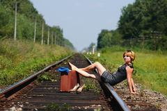 Girl on the railroad track with suitcase Royalty Free Stock Photo
