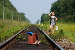 Girl on the railroad track with suitcase Stock Photography