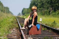 Girl on the railroad track with suitcase Stock Photo