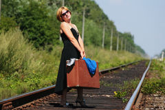 Girl on the railroad track with suitcase Royalty Free Stock Images