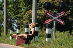 Girl on the railroad track with suitcase Stock Photos