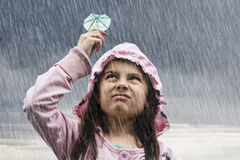 Girl in rain. A little girl holding a cocktail umbrella in the rain Stock Photo