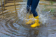 Girl with rain boots jumps into a puddle. Girl wearing yellow rain boots and navy jeans jumping into a puddle Royalty Free Stock Images