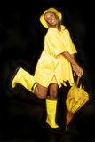 Girl in rain gear. Yellow rain gear on black backdrop Stock Photo