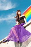 Girl on rainbow. Bright colorful portrait of young brunette female model wearing bright purple skirt, black lace top and violet shoes sitting on wall against Stock Photography