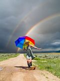 Girl and a rainbow. Girl splashing water in a puddle after a rain Stock Photos