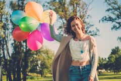 Girl with rainbow-colored air balloons in a park. Royalty Free Stock Photo