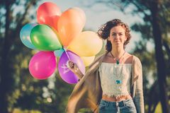 Girl with rainbow-colored air balloons in a park. Stock Photography