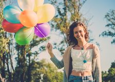 Girl with rainbow-colored air balloons in a park. Stock Photos