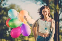 Girl with rainbow-colored air balloons in a park. Royalty Free Stock Images