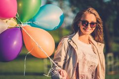 Girl with rainbow-colored air balloons in a park. Royalty Free Stock Photos