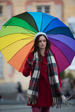 Girl with Rainbow Umbrella. Beautiful and stunning french girl taking a walk through town with her amazing colorful rainbow umbrella, wearing a long warm red Stock Photography
