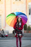 Girl with Rainbow Umbrella. Beautiful and stunning french girl taking a walk through town with her amazing colorful rainbow umbrella, wearing a long warm red Royalty Free Stock Photography