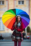 Girl with Rainbow Umbrella. Beautiful and stunning french girl taking a walk through town with her amazing colorful rainbow umbrella, wearing a long warm red Royalty Free Stock Image