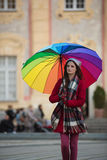 Girl with Rainbow Umbrella. Beautiful and stunning french girl taking a walk through town with her amazing colorful rainbow umbrella, wearing a long warm red Royalty Free Stock Images