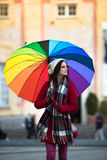 Girl with Rainbow Umbrella. Beautiful and stunning french girl taking a walk through town with her amazing colorful rainbow umbrella, wearing a long warm red Stock Photos