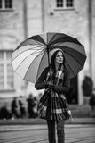 Girl with Rainbow Umbrella. Black and white photo of a beautiful and stunning french girl taking a walk through town with her amazing colorful rainbow umbrella Stock Photography
