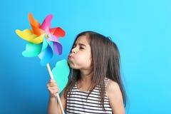 Girl with rainbow whirligig. Beautiful little girl with rainbow whirligig on blue background Stock Photo