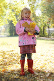 Girl in raincoat and boots in autumn park Royalty Free Stock Images