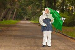 Girl in raincoat with umbrella Stock Photos