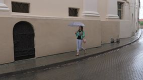 The girl in rainy weather goes under an umbrella on a narrow street of the city. A young girl walks in rainy weather under an umbrella. Go down the narrow stock video
